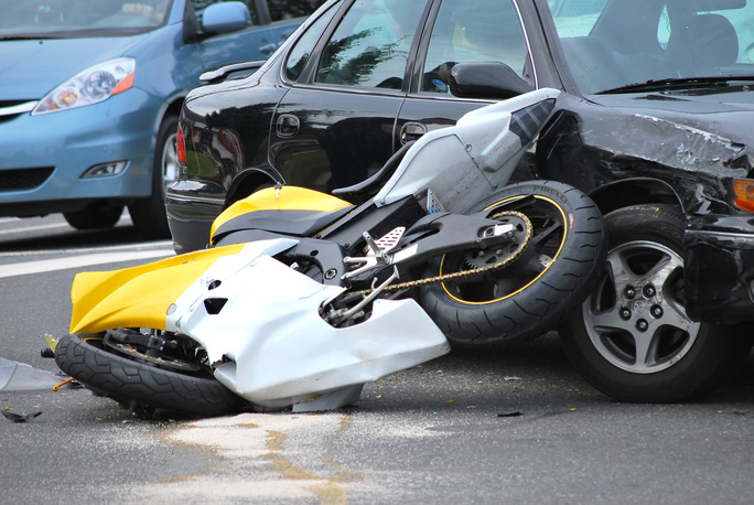Car and motorcycle accident outdoors.