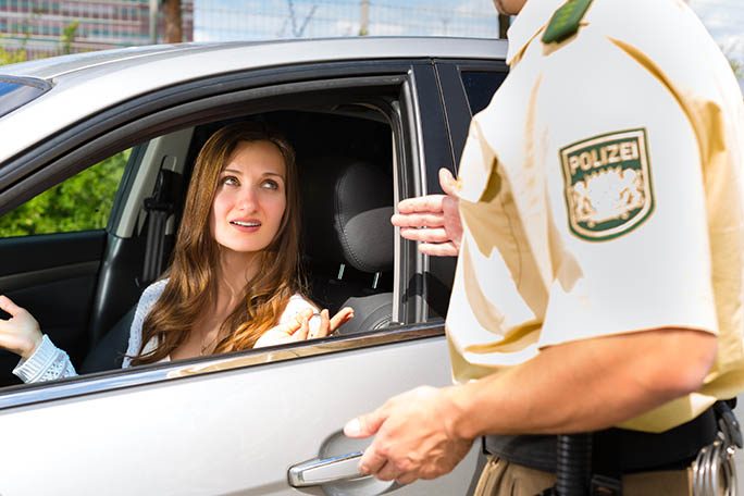 Police - young woman with policeman or cop on the street or traffic